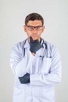 Arts in witte laag met kin op zijn hand steunend stethoscoop en geconcentreerd het kijken