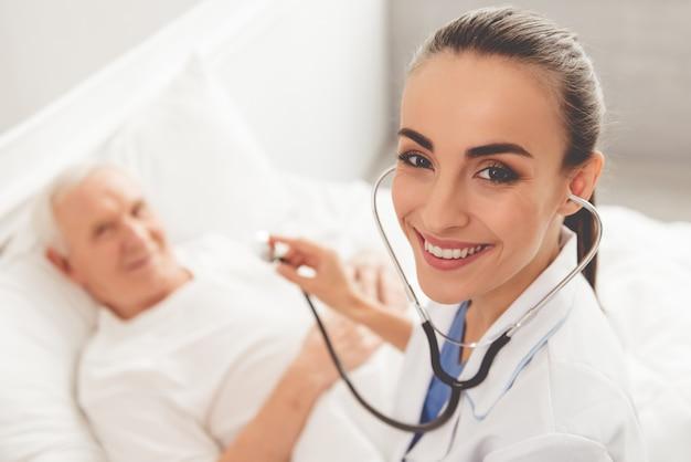 Arts in witte medische jas controleert haar oude patiënt