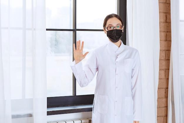 Arts in zwart masker en bril bij het raam staan en iets tegenhouden.