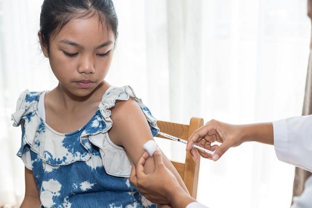 Arts injecteren in de arm van aziatisch meisje