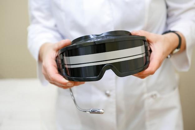Arts jas houden glazen voor kleur-pulse therapie, close-up