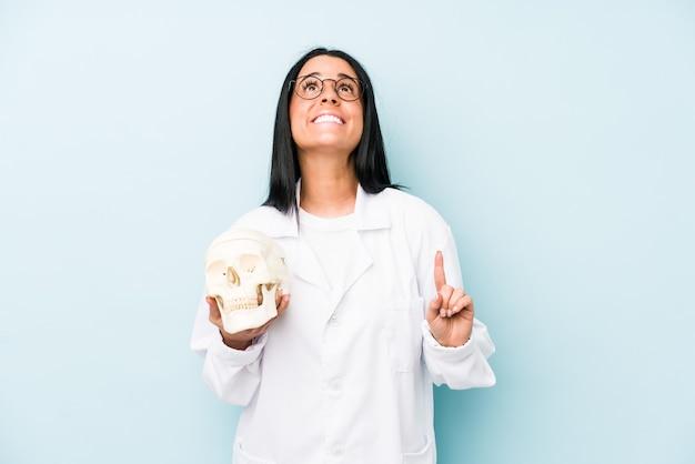 Arts kaukasische vrouw die op blauwe muur wordt geïsoleerd die ondersteboven met geopende mond richt.