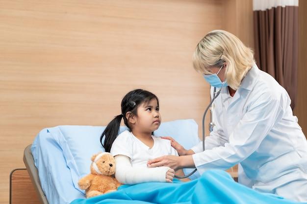 Arts kinderarts behandeling van een klein meisje patiënt op bed met teddybeer door stethoscoop