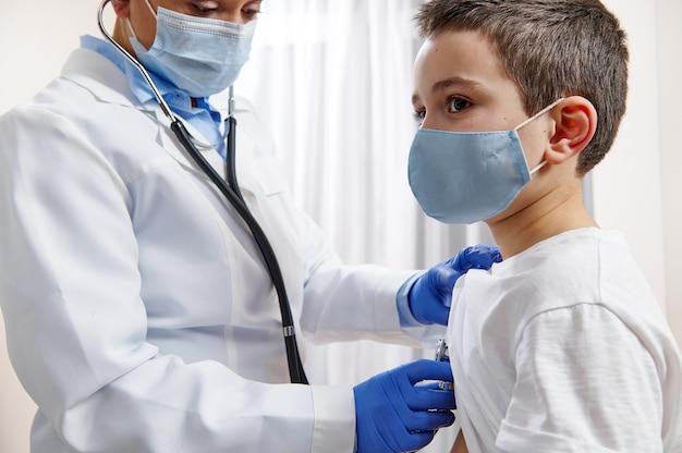 Arts-kinderarts in medisch uniform gebruikt een stethoscoop terwijl hij een kleine jongen in een beschermend medisch masker ausculteert