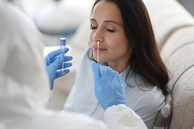Arts laboratoriumassistent in beschermend pak neemt wattenstaafje uit neus van zieke patiënt thuis
