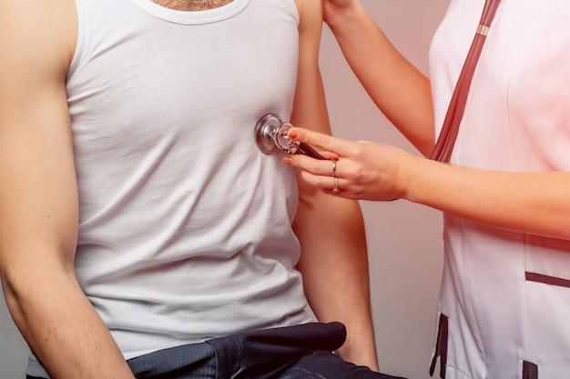 Arts luistert naar jonge patiënt borst met stethoscoop.