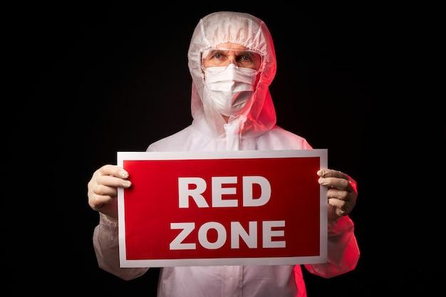 Arts man in beschermende medische pak tablet met rode zone inscriptie te houden