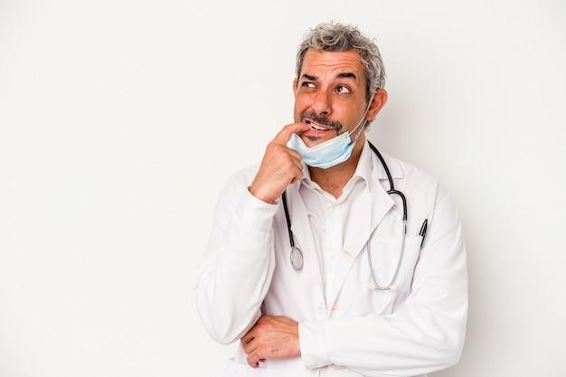 Arts man van middelbare leeftijd met een masker voor virus geïsoleerd op een witte achtergrond ontspannen denken over iets kijken naar een kopie ruimte.