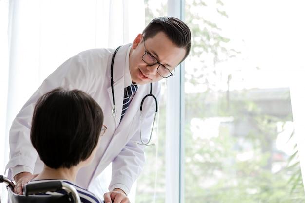 Arts man zorgen oude patiënt uitgeschakeld op rolstoel kijken uit raam