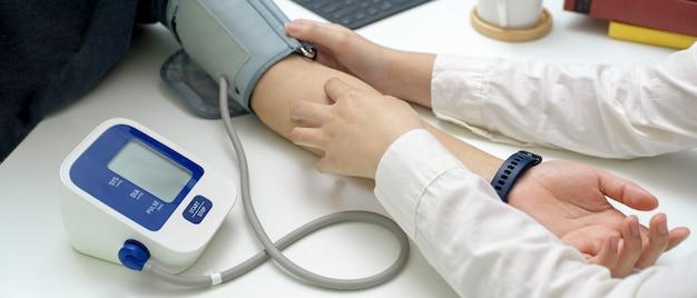 Arts medische controle haar patiënt met drukmeting in onderzoeksruimte