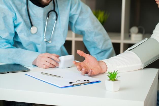Arts meet de druk van de patiënt in de kliniek