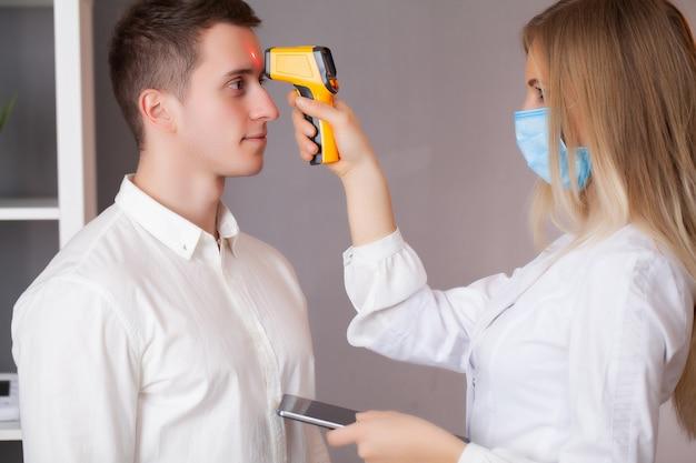 Arts meet de temperatuur van een patiënt tijdens een epidemie covid-19.