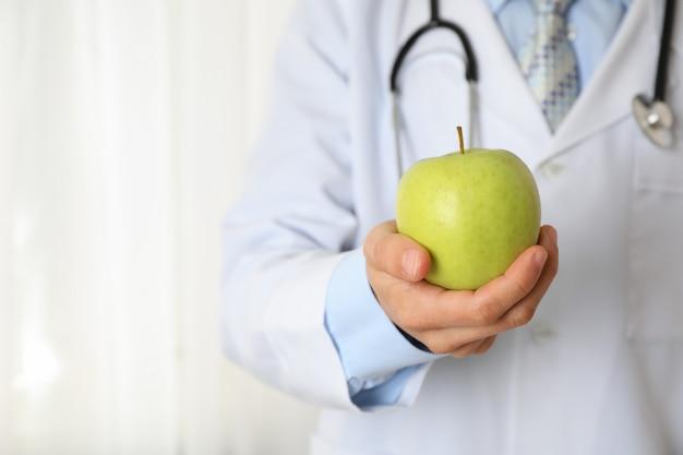 Arts met appel en stethoscoop, close-up en ruimte voor tekst