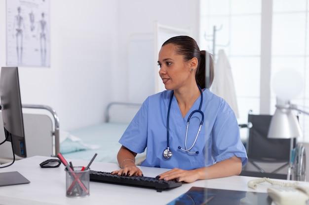 Arts met behulp van computer in ziekenhuis kantoor. gezondheidszorg arts met behulp van computer in moderne kliniek kijken naar monitor, geneeskunde, beroep, scrubs.