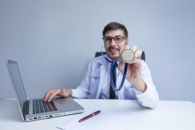 Arts met behulp van digitale tablet zoeken medische geschiedenis van de patiënt in het ziekenhuis. arts die een stethoscoop gebruikt voor onderzoek.