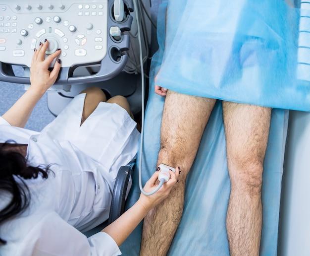 Arts met behulp van echografie-machine die de gewonde knie onderzoekt