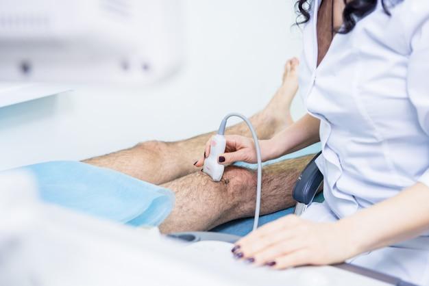 Arts met behulp van echografie-scanapparaat gewonde knie te onderzoeken.