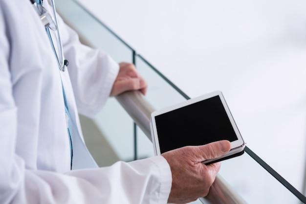 Arts met behulp van een digitale tablet in de doorgang in het ziekenhuis