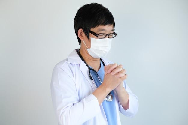 Arts met beschermend masker bidden