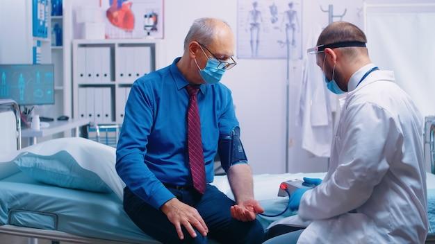 Arts met beschermende uitrusting die de bloeddruk controleert aan oude gepensioneerde senior man met masker zittend op ziekenhuisbed in moderne privékliniek tijdens covid-19-crisis. medische zorg geneeskunde examen
