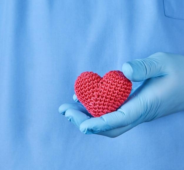 Arts met blauwe latexhandschoenen die een rood hart houden