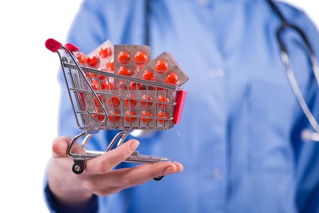 Arts met boodschappenwagentjehoogtepunt van pillen op wit wordt geïsoleerd dat