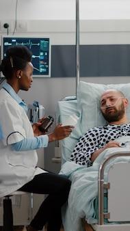 Arts met donkere huid uitleg over pillenbehandeling tegen pijn tijdens medisch onderzoek in ziekenhuisafdeling