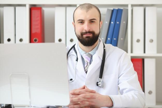 Arts met een baardzitting bij het bureau in het bureau