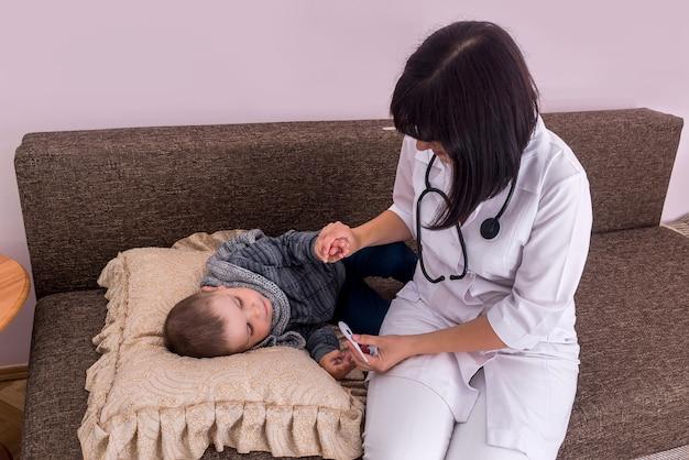 Arts met een kleine patiënt die koorts heeft