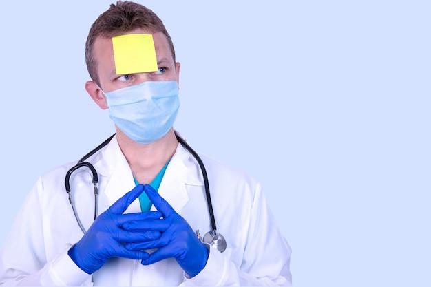 Arts met een lege gele kleverige herinnering prielyinom op zijn voorhoofd. het concept van ethiek en herinneringen aan het dragen van een medisch, beschermend wegwerpmasker op openbare plaatsen.
