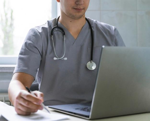 Arts met een stethoscoop die aan laptop werkt