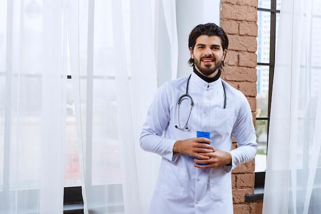 Arts met een stethoscoop die een chemische kolf met blauwe vloeistof erin houdt.