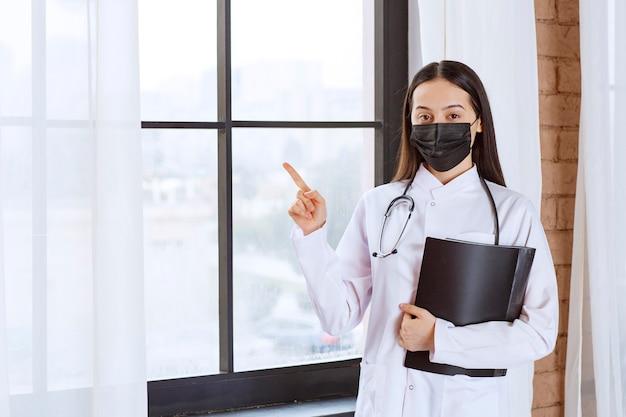 Arts met een stethoscoop en een zwart masker staat naast het raam en houdt een zwarte geschiedenismap van de patiënten vast terwijl hij ergens naar wijst.