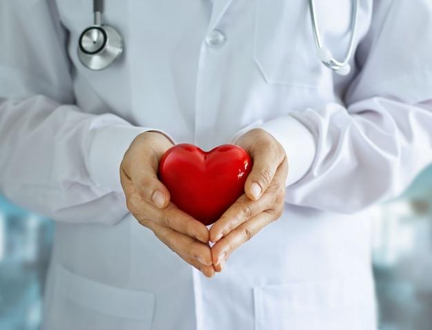 Arts met een stethoscoop en rood hart vorm in handen op ziekenhuis achtergrond