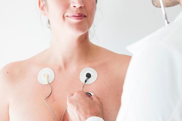 Arts met een stethoscoop in de buurt van vrouw met elektroden