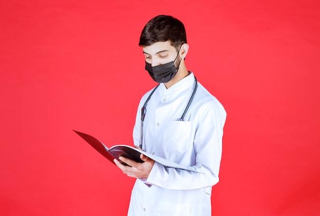 Arts met een zwart masker die een zwarte map vasthoudt en leest.