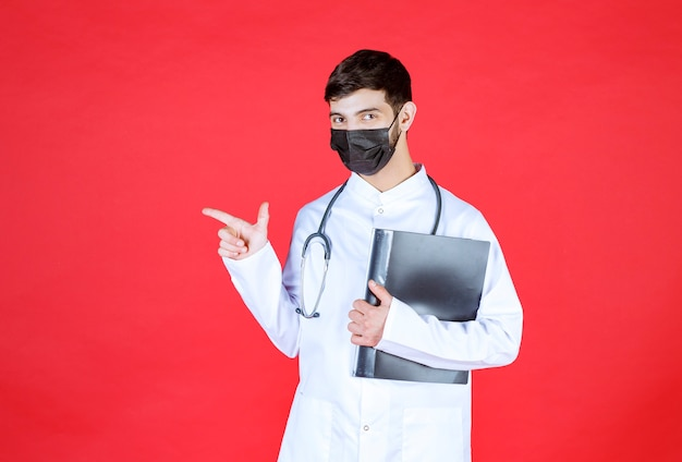 Arts met een zwart masker die een zwarte map vasthoudt en naar iemand wijst.