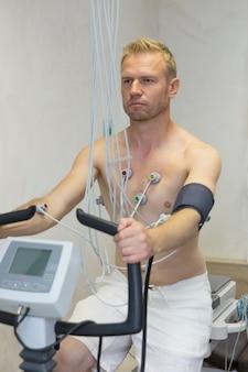 Arts met elektrocardiogramapparatuur die de test van de cardiogramfiets maken aan mannelijke patiënt in het ziekenhuiskliniek