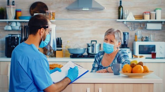 Arts met gezichtsmasker die tijdens huisbezoek met senior vrouw over coronaviruspandemie bespreekt en aantekeningen maakt. verpleegkundige maatschappelijk werker bij gepensioneerd senior koppelbezoek dat de verspreiding van covid-19 uitlegt,