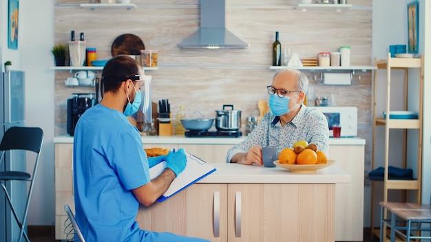 Arts met gezichtsmasker en vizier die recept op klembord schrijft tijdens patiënthuisbezoek. verpleegkundige maatschappelijk werker bij bezoek aan gepensioneerd senior echtpaar met uitleg over de verspreiding van covid-19, hulp voor mensen in r