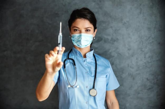Arts met gezichtsmasker spuit met vaccin te houden