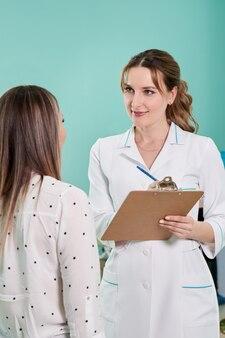 Arts met klembord en jonge vrouwelijke patiënt die zich in zaal van moderne kliniek bevindt
