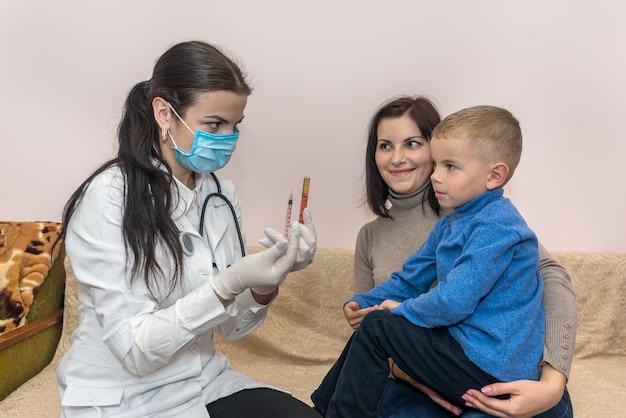 Arts met medicatie in spuit en jongen met moeder