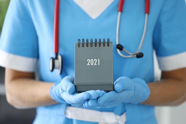 Arts met phonendoscope om zijn nek houdt bureaukalender in rubberen handschoenen