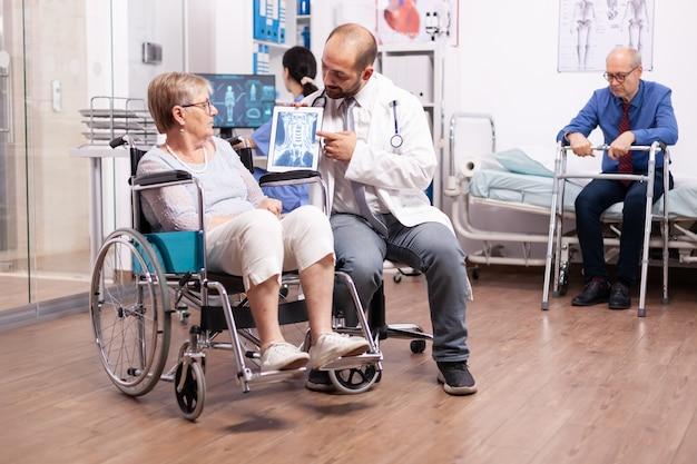 Arts met stethoscoop die tablet-pc gebruikt tijdens onderzoek van gehandicapte vrouw in rolstoel