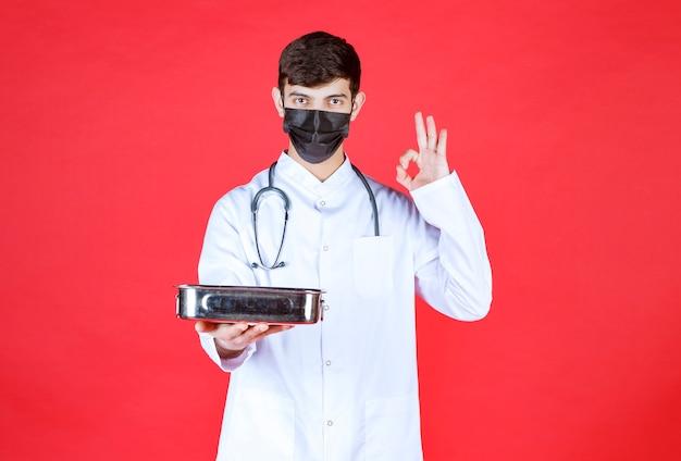Arts met stethoscoop in zwart masker die een metalen container met gereedschap vasthoudt en een teken van plezier toont.