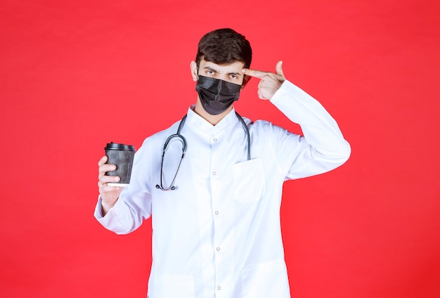 Arts met stethoscoop in zwart masker die een zwarte afhaalkoffiekop houdt en denkt.