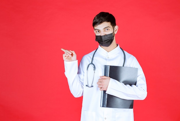 Arts met stethoscoop in zwart masker die een zwarte map met patiëntgeschiedenissen vasthoudt en naar iemand wijst.