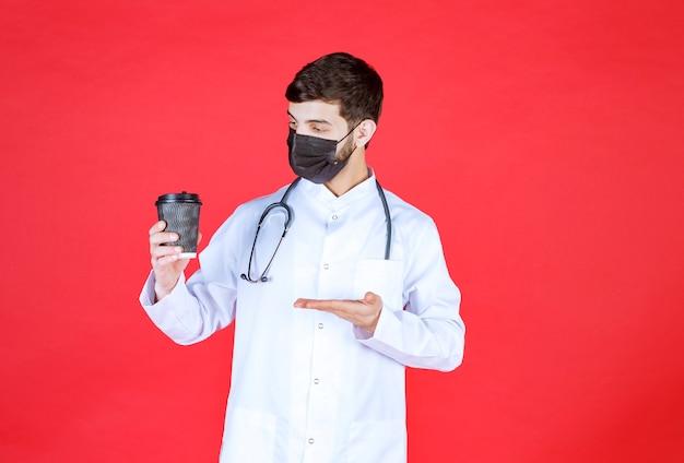 Arts met stethoscoop in zwart masker met een zwarte afhaalmaaltijden koffiekopje.