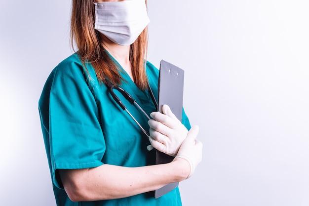 Arts met stethoscoop op witte achtergrond en gezichtsmasker die een rapport houden. onherkenbare vrouwelijke arts. ziekenhuis geneeskunde concept